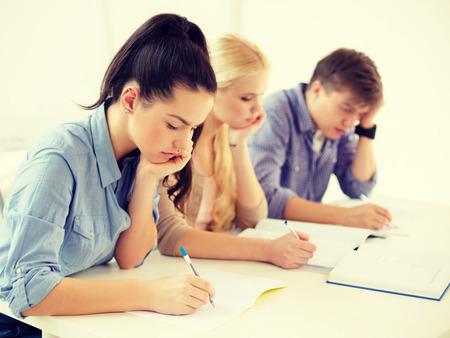 school en onderwijs concept - groep vermoeide studenten met notebooks op school