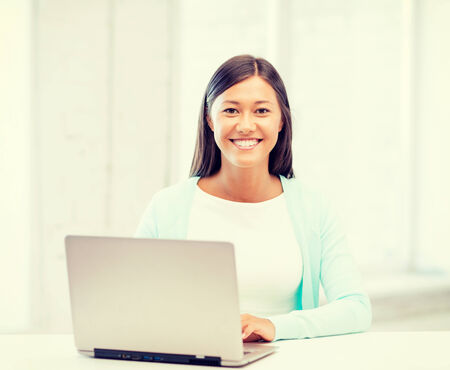 education concept - smiling international student girl with laptop at school photo