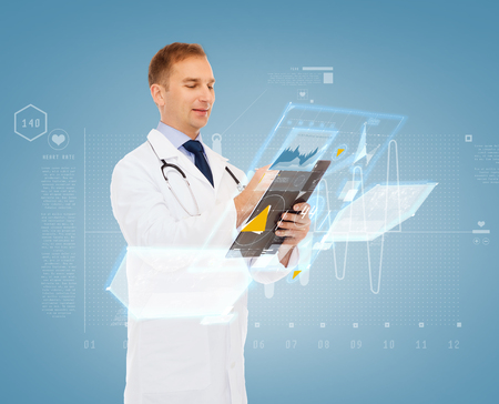 medicine, profession, future technology and healthcare concept - smiling male doctor with clipboard and stethoscope writing prescription over blue background Stock Photo