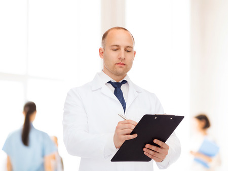 serious doctor: medicine, profession, teamwork and healthcare concept - serious male doctor with clipboard writing prescription over group of medics Stock Photo