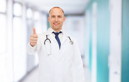healthcare, profession, gesture and medicine concept - smiling male doctor with stethoscope showing thumbs up over hospital background photo