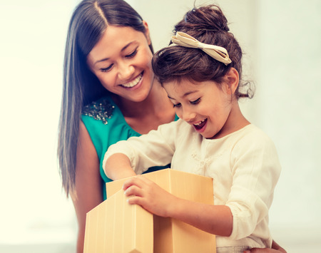 holidays, presents, christmas, birthday concept - happy mother and child girl with gift box photo