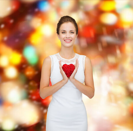 happiness, health, charity and love concept - smiling woman in white dress with red heart over party lights background photo