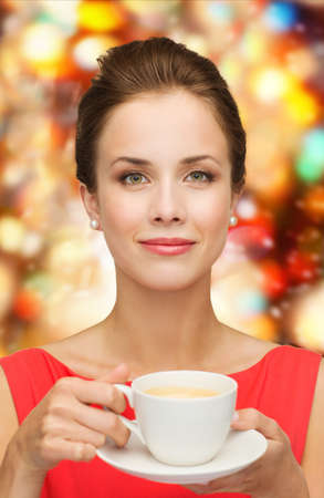 leisure, happiness, holidays and drink concept - smiling woman in red dress with cup of coffee over shiny lights background photo