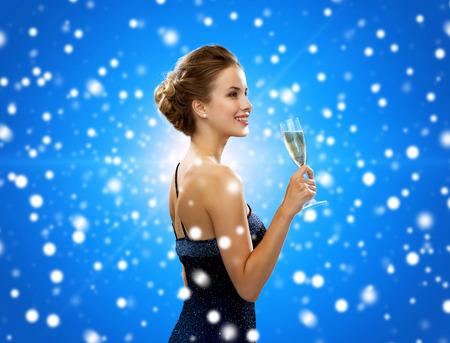 vestido de noche: fiesta, bebidas, días de fiesta, lujo y celebración concepto - mujer sonriente en traje de noche con un vaso de vino espumoso sobre fondo azul cubierto de nieve
