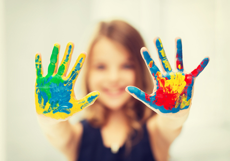 kids painted hands: education, school, art and painitng concept - little student girl showing painted hands