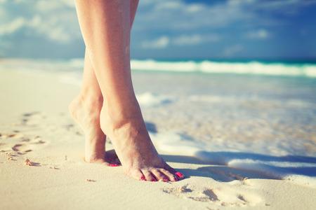 uñas pintadas: verano, playa, ocio y parte el concepto del cuerpo - de cerca de piernas de la mujer en la orilla del mar