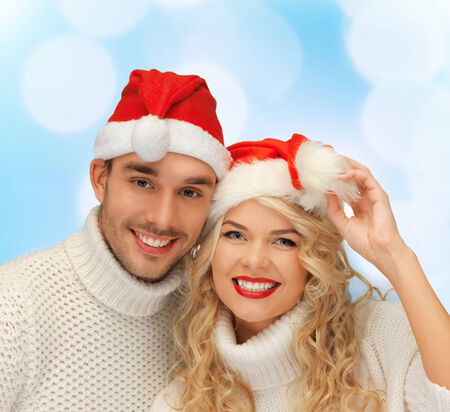winter, holidays, christmas and people concept - smiling couple in sweaters and santa helper hats over blue lights background photo