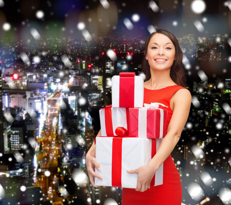 christmas, winter, happiness, holidays and people concept- smiling woman with gift boxes over snowy night city background photo