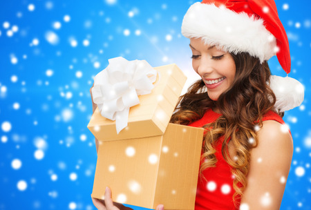 christmas, holidays, celebration and people concept - smiling woman in red dress with gift box over blue snowy background photo