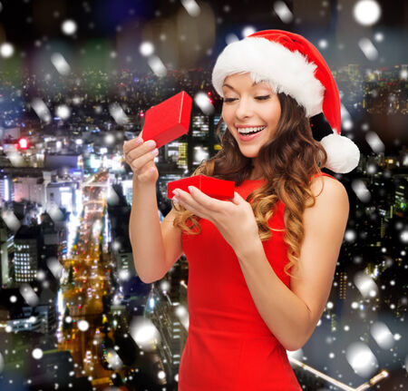 fancy box: christmas, winter, happiness, holidays and people concept- smiling woman in santa helper hat with gift box over snowy night city background