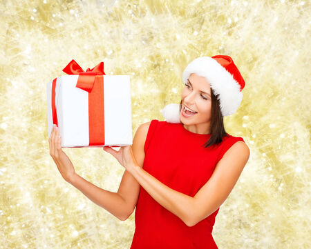 santa helper: christmas, holidays, celebration and people concept - smiling woman in red dress with gift box over yellow lights background
