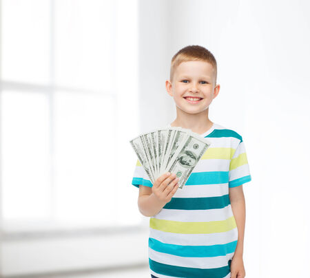 financial, planning, childhood and concept - smiling boy holding dollar cash money in his hand over white room background photo