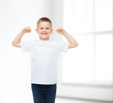 arms raised: advertising, people, gesture and childhood concept - smiling little boy in white blank t-shirt with raised hands over white room background Stock Photo