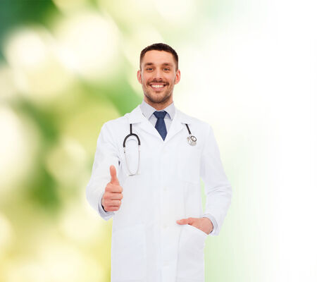 healthcare, profession and medicine concept - smiling male doctor with stethoscope showing thumbs up over white background photo