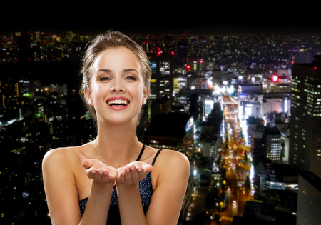 people, holidays, advertisement and luxury concept - laughing woman in evening dress holding something imaginary over night city background photo