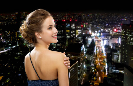 chic woman: people, holidays and glamour concept - smiling woman in evening dress over black background over night city background from back