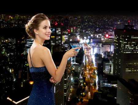 party, drinks, holidays, luxury and celebration concept - smiling woman in evening dress holding cocktail over night city background photo