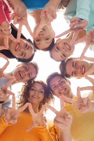 friendship, youth, gesture and people - group of smiling teenagers in circle showing victory sign Archivio Fotografico