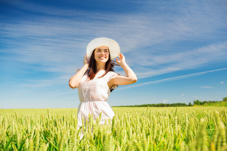 happiness, nature, summer, vacation and people concept - smiling young woman wearing straw hat on cereal field photo