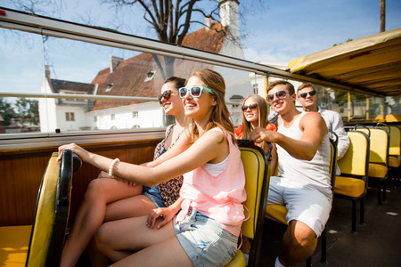 traveling: friendship, travel, vacation, summer and people concept - group of smiling friends traveling by tour bus