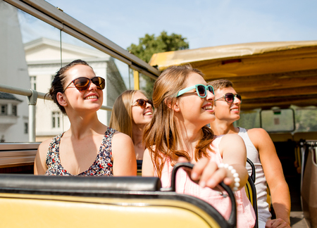friendship, travel, vacation, summer and people concept - group of smiling friends traveling by tour bus photo