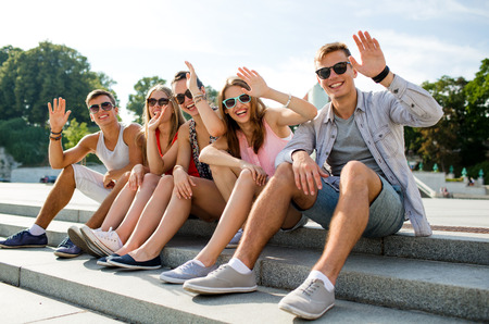 friendship, leisure, summer, gesture and people concept - group of smiling friends sitting on city street and waving hands Banco de Imagens - 31275867