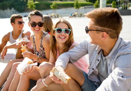 comida rapida: la amistad, el ocio, el verano y el concepto de la gente - grupo de amigos sonrientes en gafas de sol que se sientan con la comida en la plaza de la ciudad Foto de archivo