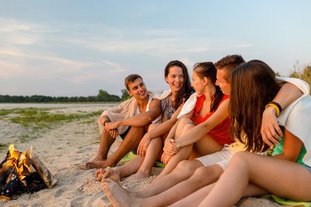 friendship, happiness, summer vacation, holidays and people concept - group of smiling friends sitting near fire on beach photo