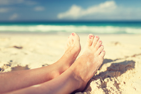 bare feet toes: summer, beach, leisure and body part concept - closeup of woman legs on sea shore Stock Photo