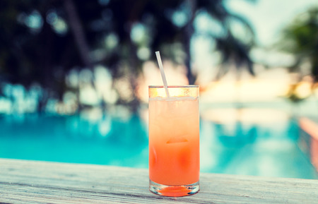 summer, beach, drink, cocktail and leisure concept - cocktail drink on tropical beach photo