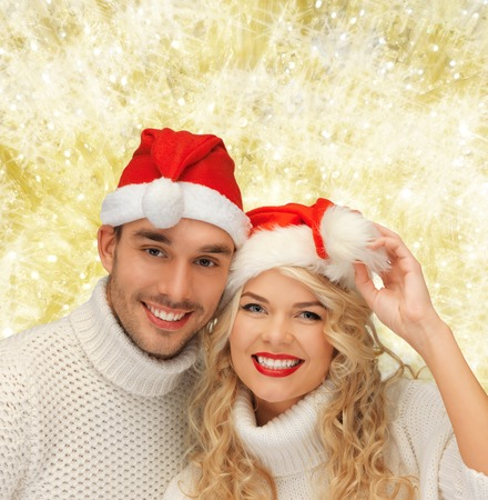 winter, holidays, christmas and people concept - smiling couple in sweaters and santa helper hats over yellow lights background photo