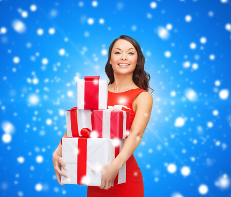 christmas, holidays, valentines day, celebration and people concept - smiling woman in red dress with gift boxes over blue snowy background photo