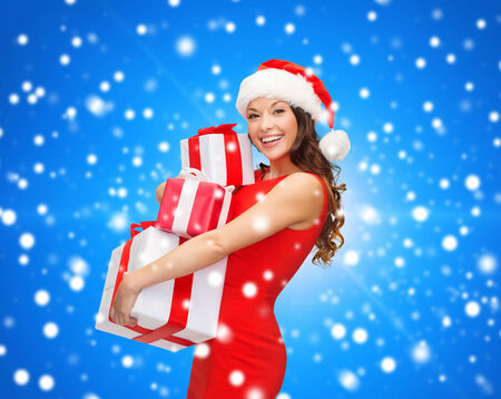 christmas, holidays, celebration and people concept - smiling woman in red dress with gift boxes over blue snowy background photo