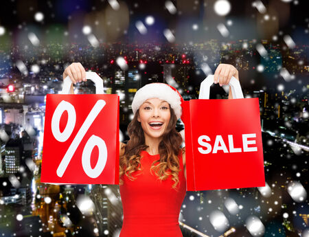 sale, gifts, christmas, holidays and people concept - smiling woman in red dress with shopping bags and percent sign over city background photo