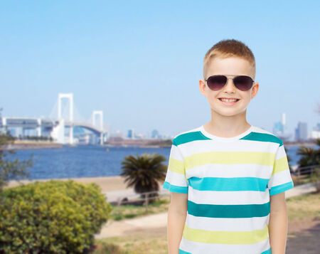 happiness, summer, travel, childhood and people concept - smiling cute little boy in sunglasses photo