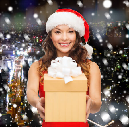 christmas, winter, happiness, holidays and people concept- smiling woman in santa helper hat with gift box over snowy night city background photo