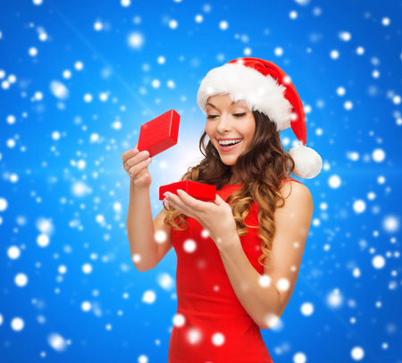 christmas, holidays, celebration and people concept - smiling woman in red dress with small gift box over blue snowy background photo