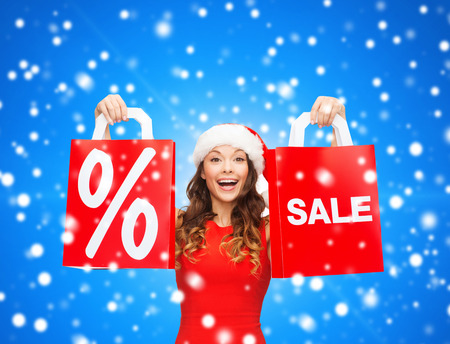sale, gifts, christmas, holidays and people concept - smiling woman in red dress with shopping bags and percent sign on them over blue snowy background photo