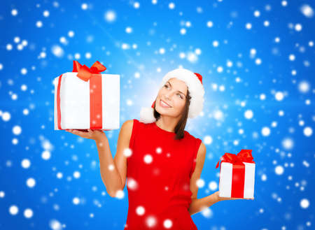 christmas, holidays, valentines day, celebration and people concept - smiling woman in red dress with gift box over blue snowy background photo