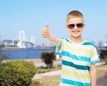 happiness, summer, childhood, gesture and people concept - smiling cute little boy in sunglasses showing thumbs up over city background photo