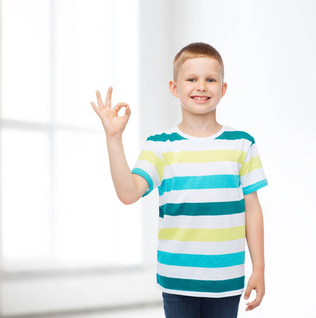 childhood, home, gesture and people concept - smiling little boy in casual clothes making ok gesture over white room background photo