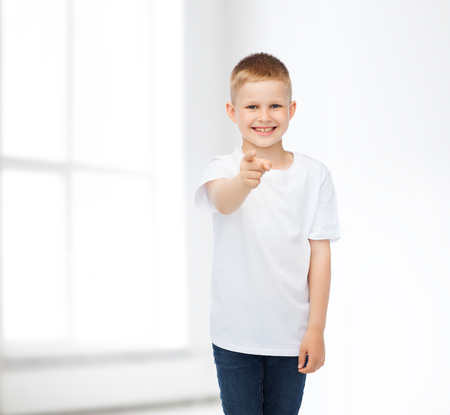 advertising, people, home, gesture and childhood concept - smiling little boy in white blank t-shirt pointing finger at you over white room background photo