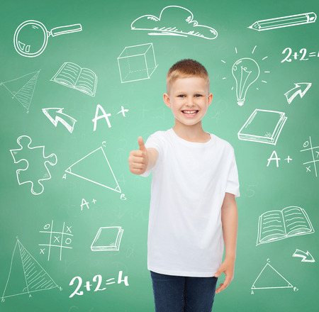 childhood, gesture, education, advertisement and people concept - smiling boy in white t-shirt showing thumbs up over green board with doodles background photo