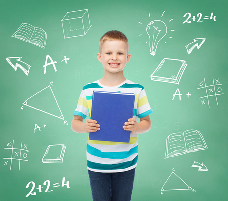 education, childhood and school concept - smiling little student boy with book over green board with doodles background photo