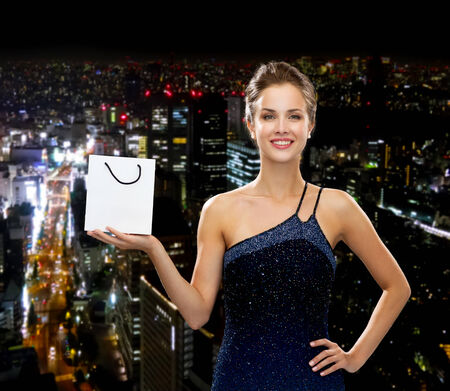 holydays: luxury, advertisement, holydays and sale concept - smiling woman with white blank shopping bag over night city background Stock Photo