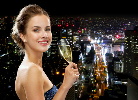 party, drinks, holidays, luxury and celebration concept - smiling woman in evening dress with glass of sparkling wine over night city background photo