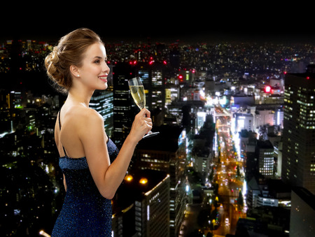 celebrating: party, drinks, holidays, luxury and celebration concept - smiling woman in evening dress with glass of sparkling wine over night city background