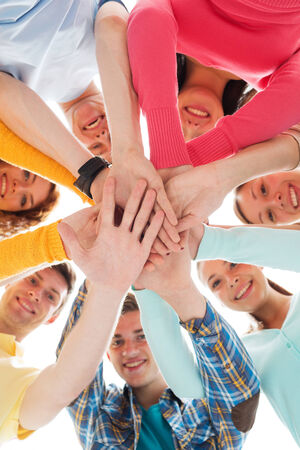 agreeing: friendship, youth and people concept - group of smiling teenagers with hands on top of each other