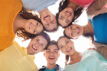 la amistad, la juventud y la gente - grupo de adolescentes sonrientes en círculo Foto de archivo